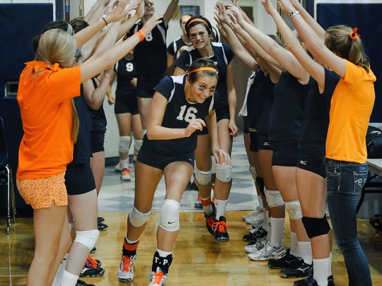 Mercy's Emma Falk (16) is shown here coming onto the court before a volleyball match early in her senior season in 2012. It was her first start after missing her junior season while overcoming cancer for a second time.
