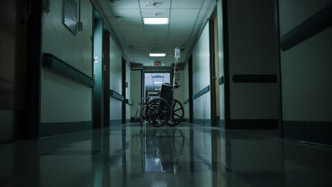 Empty wheelchair and intravenous drip in hospital corridor