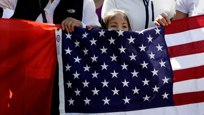 A young girl helps hold a U.S. flag as a group marches through downtown Austin heading to the Texas Capitol during a Day Without Immigrants protest Feb. 16, 2017.