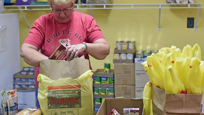 Volunteer Gabriele Mitchell of Help & Hope Ministries assembles a bag of various foods on Tuesday.