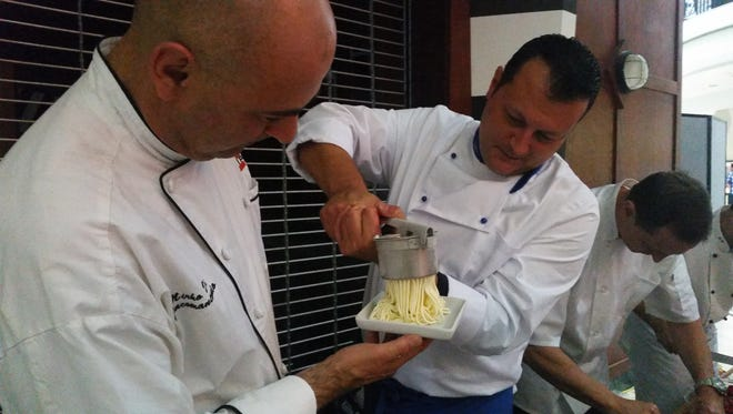 """Gelato chef Rudi Sacchet grinds spaghetti-style Gelato onto a plate held by chef Mirko Di Giacomantonio. In 2015, the Centre of Tallahassee announced a new food concept called the """"Urban Food Market,"""" featuring several Italian-themed restaurants under one roof."""