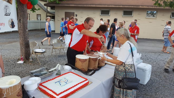 Gospel Tide board member Bill Strausbaugh and his wife Sandy serve cake and ice cream to Mrs. Ruth Lehman at the Tide Global Radio Ministry party.