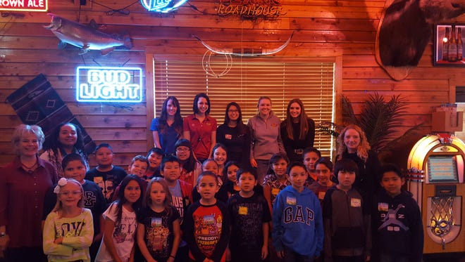 Apache Elementary School students in Nancy Brummell's third-grade class pose with staff at the Texas Roadhouse restaurant in Farmington on Jan. 5 after winning a school-wide reading contest. The students learned line dancing and made dinner rolls in the restaurant's kitchen.