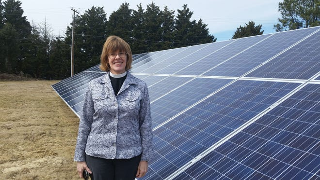 The Very Rev. Frieda Malcolm, rector of St. Alban's Episcopal Church in Salisbury, stands by one of three solar arrays recently installed in front of the church.