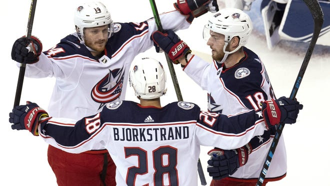 Blue Jackets right wing Oliver Bjorkstrand is congratulated by teammates Gustav Nyquist, left, and Pierre-Luc Dubois after scoring in the first period.