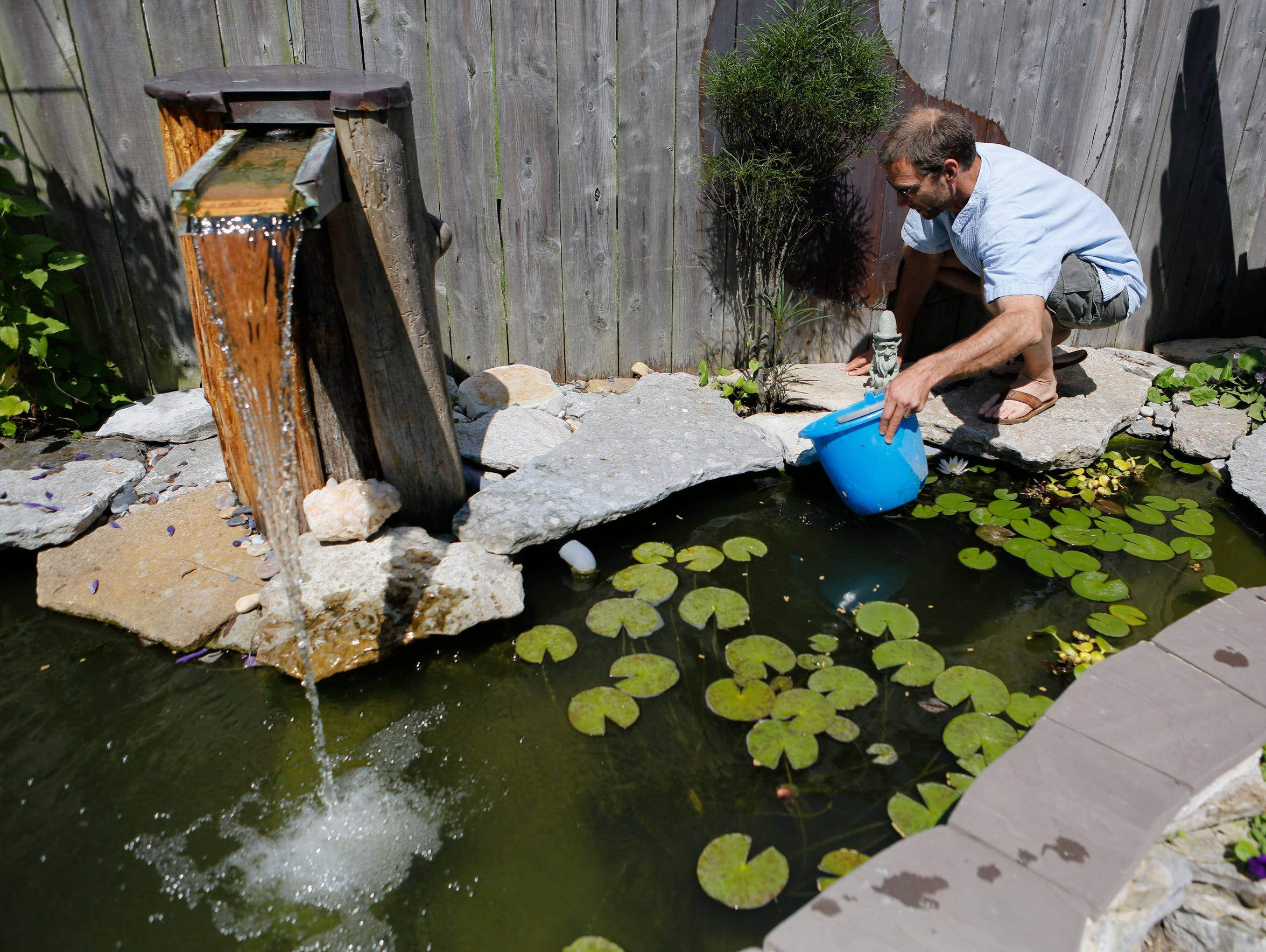 Joe scoops up pond water to give to other plants in