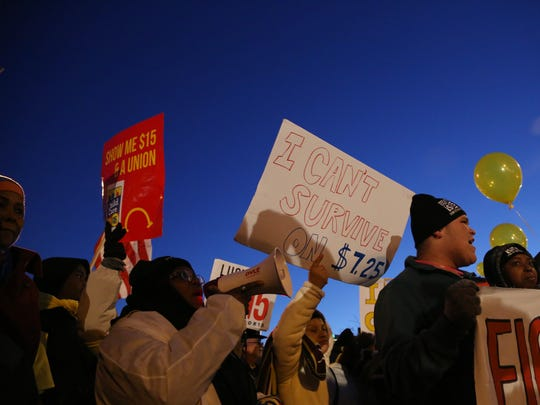A group of fast-food workers, home care and child care workers, and community supporters march through the streets of Des Moines on Thursday, Jan. 28, 2016, to the steps of the Iowa Events Center, where the final GOP debate before the Iowa Caucus was being held. The workers were marching in support of a higher minimum wage and a union.