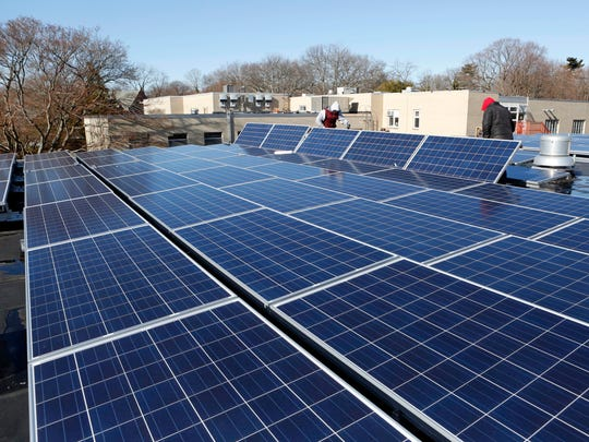 Erik Spoerle, left, and Kai Horton of SunBlue Energy, a Sleepy Hollow based company, installs solar panels on the roof of a Westchester Day School building in Mamaroneck.