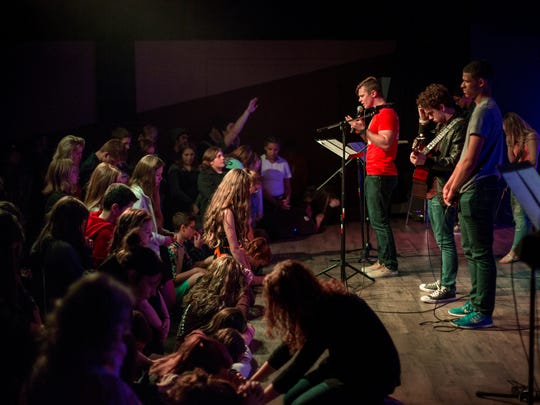 Youth Pastor Spencer Olson leads a prayer during a weekly service May 4 at the Impulse Student Ministries youth center..