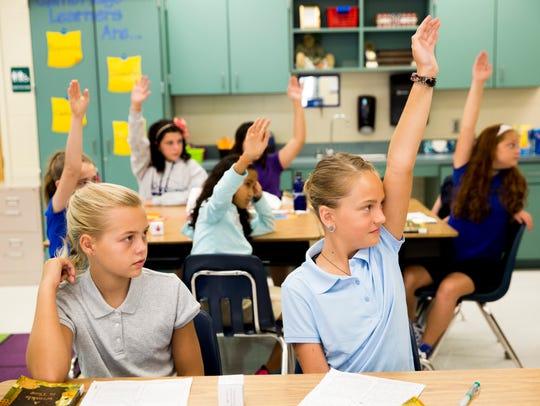 Fifth-grade students raise their hands in Maureen Zaranek's