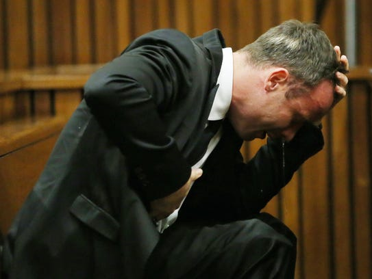 South African Paralympic track star Oscar Pistorius reacts as he listens to evidence by a pathologist during his trial in court in Pretoria on April 7, 2014. As the defence opens its case, the 27-year-old Paralympian will give the court his first account of why he shot dead his model girlfriend Reeva Steenkamp in the early hours of Valentine's Day in 2013.  AFP PHOTO / POOL / THEMBA HADEBETHEMBA HADEBE/AFP/Getty Images