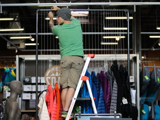 REI employee Michael Sarbello sets up a display of jackets in preparation for the stores grand opening Friday in the Christiana Fashion Center.