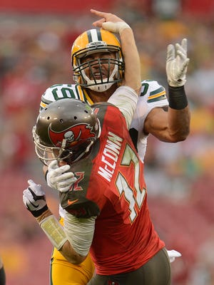 Green Bay Packers linebacker Brad Jones (59) puts a hit on Tampa Bay Buccaneers quarterback Josh McCown (12) in the fourth quarter during Sunday's game at Raymond James Stadium in Tampa, Fla. McCown threw an interception on the play.