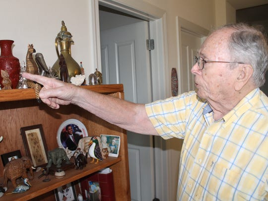 John Bird points out souvenirs he has kept from his travels around the world.