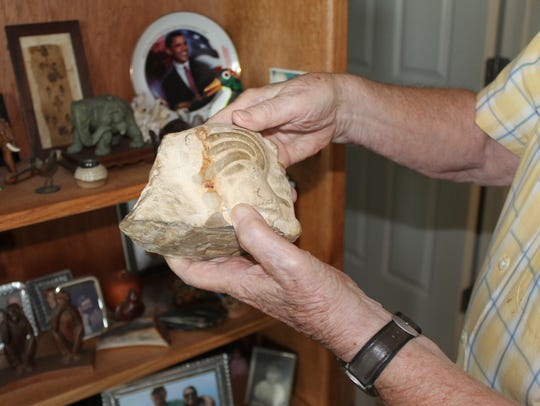 John Bird holds a carved stone from the Valley of the