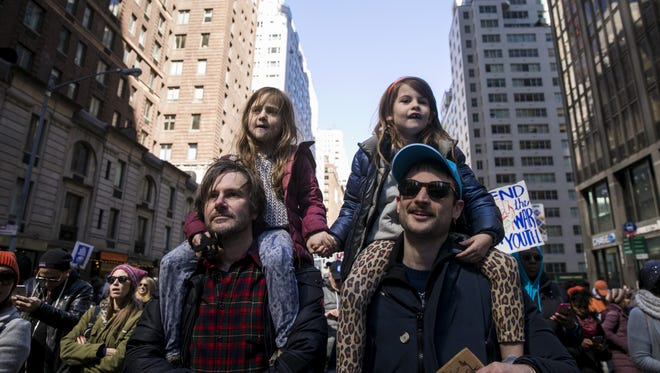 From left to right, Henrietta Hamilton, 5, and Marlowe Sturridge, 5, ride on their fathers' shoulders as they march on Sixth Avenue during the March For Our Lives, March 24, 2018, in New York City.