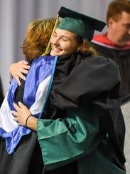 Graduate Madisen Blackford hugs retiring Principal