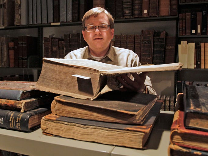 """Associate professor of church history and curator of special collections for the CTS Library Rev. Dr. Scott D. Seay shows a 16th century Bible that is too fragile to be put on display, at the Christian Theological Seminary, Thursday, May 15, 2014.  He shows the 1596 Bible which is in the rare book room at the CTS Library.  It is is written in Greek, Latin and German. An exhibit of 16th century Bibles, called """"Sacred History: Rare 16th Century Bibles,"""" is on display outside the CTS Library coinciding with the 2014 Baccalaureate and Commencement exercises."""