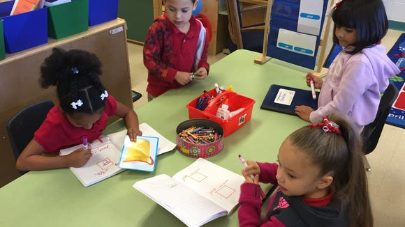Myrtle Cooper Elementary School prekindergarten students practice writing and drawing words that begin with the letter J.
