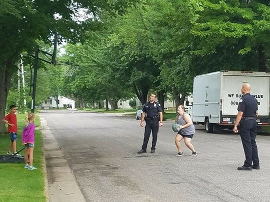 "Wisconsin Rapids Police Officer Dustin Gessert, left, and Lt. Brian Krzykowski, play basketball with two Wisconsin Rapids children and their babysitter Thursday after a ""cranky"" neighbor lady called in a complaint about the children."