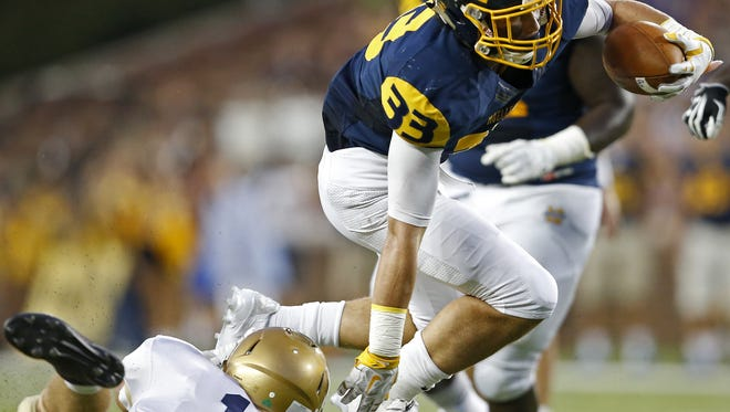 Moeller running back Hunter Hughes leaps over Indianapolis Cathedral defensive back Ben Stewart on Friday at Nippert Stadium at the University of Cincinnati.