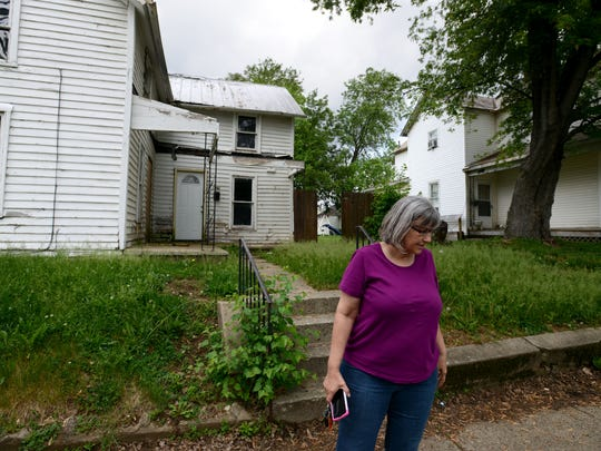 Sixth Ward Lancaster City Councilwoman Becky Tener stands in front of an abandoned and dilapidated house in Lancaster. Tener has tried to get the house, which has holes in the siding, fixed.