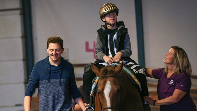 From left, IndyCar driver Stefan Wilson walks alongside as Yerick Colon, 12, has a routine horse riding session with horse Riley and therapist Sue Tribolet at The Children's TherAplay Foundation in Carmel, Ind., Tuesday, April 4, 2017. IndyCar drivers will partner with children at the therapy center for the Horsepower 500 on May 9, where drivers race adaptive tricycles to raise funds for equine-assisted physical and occupational therapy. Wilson asked Colon to be his race partner during a surprise visit to the center.