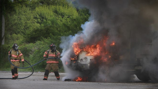 FILE: Firefighters from the Fort Myers Fire Department, work to extinguish a dump truck that burst into flames.