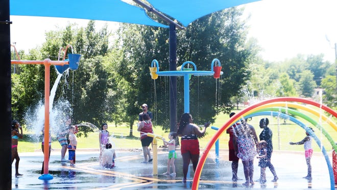 Families play in the Martin Luther King Park splash pad, Friday, June 5, 2020, under the large shade structure Fort Smith Parks and Recreation installed in April.