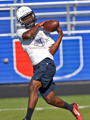 Urbandale running back Abdul Mansaray hauls in a pass at practice Tuesday. The senior, who averaged 9.7 yards a carry last fall, returns as the J-Hawks' leading rusher and receiver.