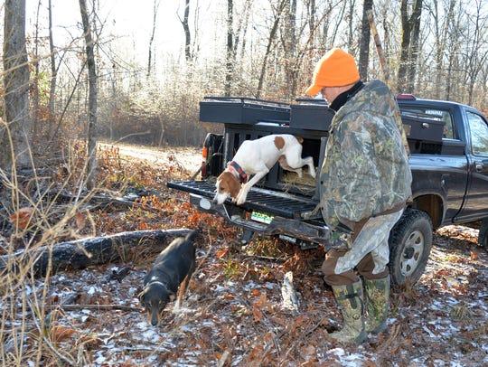 Kent Robertson unloads two deer hounds for a deer drive