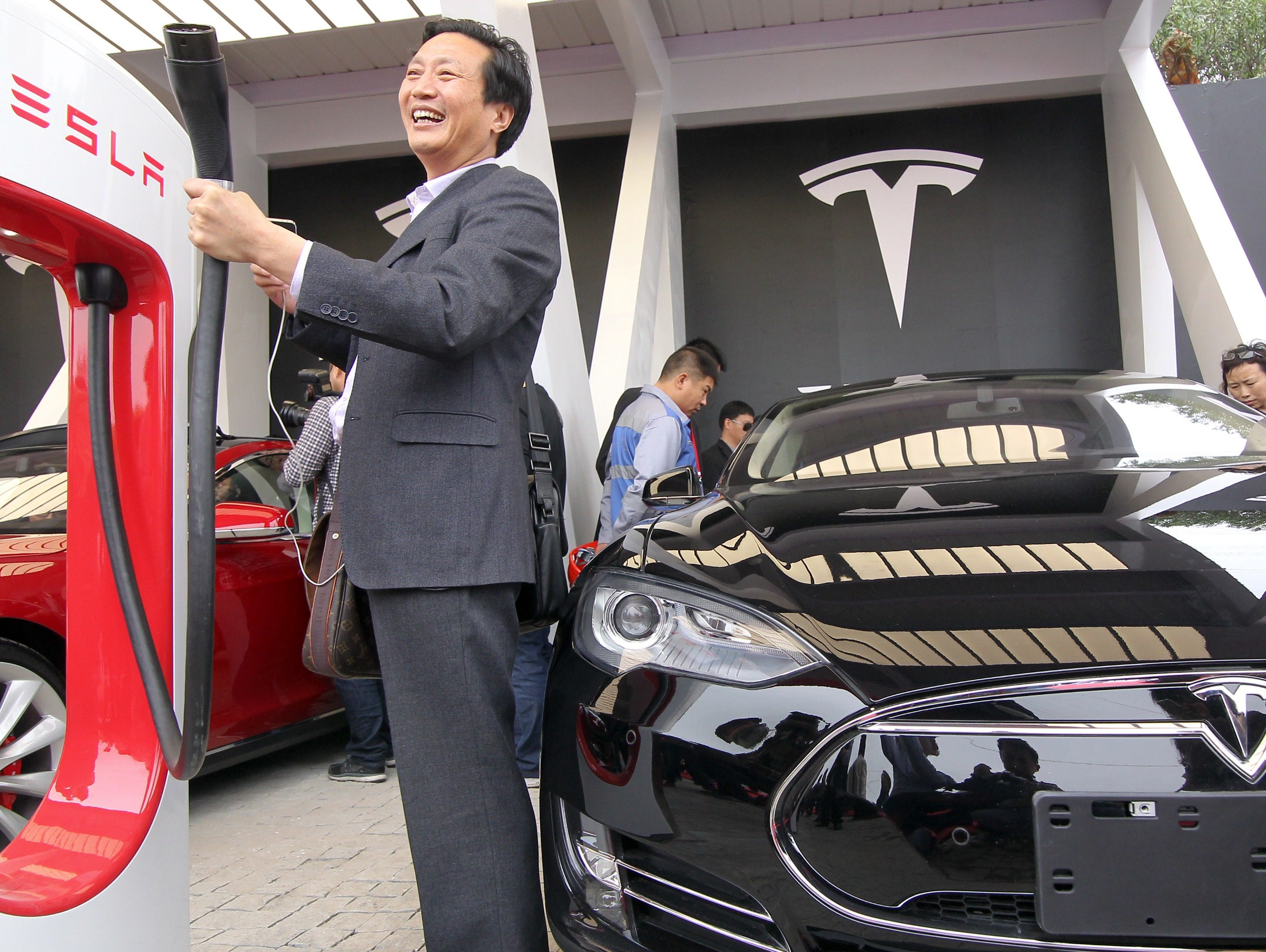 A Chinese guest poses for a photo by a Tesla