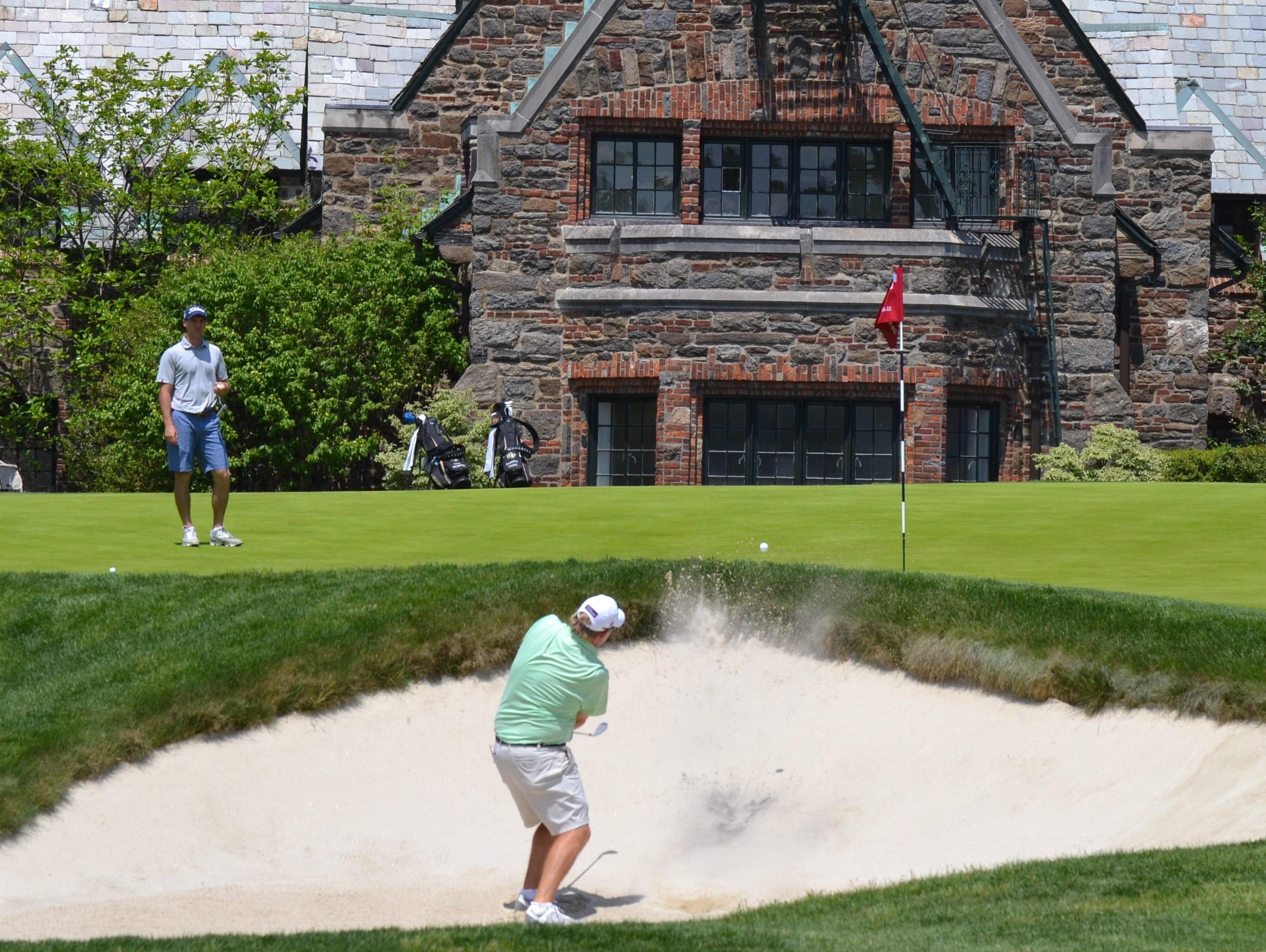 Patrick Christovich blasts out of a bunker onto the 10th green on Winged Foot East during a Round of 32 win in the U.S. Amateur Four-Ball Championship on Monday.