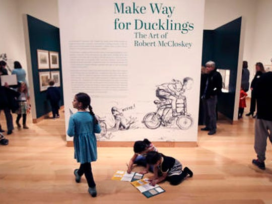 "In this Nov. 21, 2016, photo, children sit on the floor and color and sketch in a workbook featuring the classic children's story ""Make Way for Ducklings"" at an exhibit at the Museum of Fine Arts in Boston. The new exhibition is devoted to Robert McCloskey, the award-winning author of 1941's ""Make Way for Ducklings"" and other children's classics."