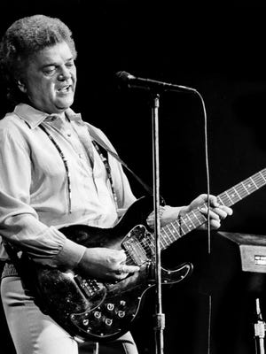 """Conway Twitty picks out """"Boogie Grass Band"""" on the guitar for the screaming fans during the """"Country Explosion"""" unofficial Fan Fair kick-off concert at Municipal Auditorium June 9, 1985."""