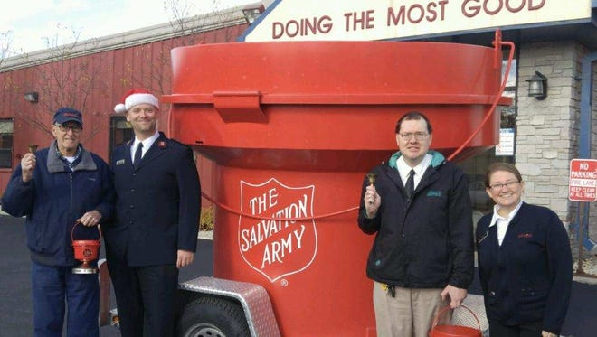"The 2017 Salvation Army Red Kettle Campaign features three Red Kettle sizes, each doing their part to raise $160,000 The Salvation Army of Fond du Lac County uses to help and serve those struggling in our community.  From left: John Pelletier holds the mini counter kettle and coordinates 91 business hosts; Captain Steve Wilson stands alongside the king-sized Red Kettle,available until Dec. 2;  Salvation Army advisory board Chairperson Scott Richter holds the full-sized kettle that stands, with bellringers, at 17 locations through Dec.23; and Captain Telinda Wilson smiles alongside Scott, inviting bellringers to go to myvoluteerpage.com, search ""Fond du Lac"" and sign up."