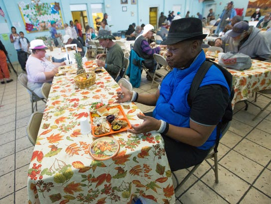 Jeromy O. Anderson sits down to enjoy a Thanksgiving Day meal at El Caldito Soup Kitchen, Thursday Nov. 23, 2017.
