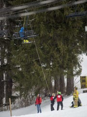 Ski patrol and emergency personnel lower skiers and