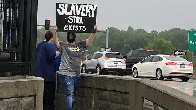 A crowd of nearly 20 people braved a downpour to protest human trafficking on the Noland Road bridge, above Interstate 70, on Thursday. Many held signs to let drivers know of the cause, such as one that says 'Slavery Still Exists.' Many travelers got ample time to view the signs as an accident on I-70 east of Noland Road led to standstill traffic during rush hour. In April, Independence Police Department and Homeland Security arrested 24 people for prostitution and human trafficking in the city, focusing on hotels at the I-70/Noland Road intersection. One missing person and four human trafficking victims were located due to the two-day sting.