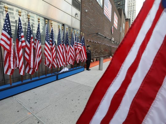 """Flags line the sidewalk outside """"Ten House"""" in lower Manhattan, home to a memorial to fallen firefighters, on Monday, the 16th anniversary of the 9/11 attacks."""