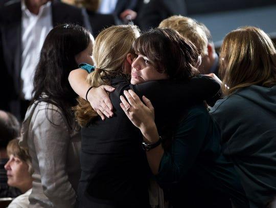 Residents greet each other before an interfaith vigil