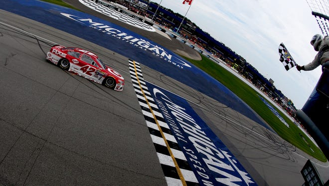 Kyle Larson takes the checkered flag to win the NASCAR Sprint Cup  Pure Michigan 400 at Michigan International Speedway.