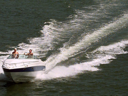 05-25-2000 1a; Two boaters make their way along San Carlos Bay just before passing under the Sanibel Causeway Wednesday afternoon. TODD STUBING/The News-Press