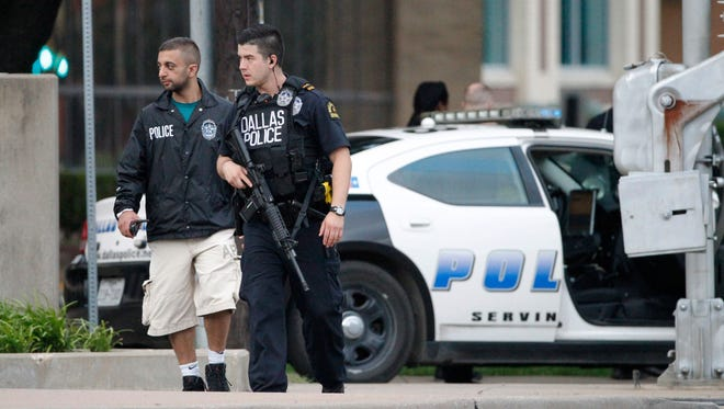 Dallas police officers walk down Belleview Street one block away from police headquarters searching the area Saturday June 13, 2015, in Dallas. A police sniper shot a man suspected of an overnight attack on police headquarters and the department was checking to see if he's still alive, Police Chief David Brown said Saturday.  (AP Photo/Tony Gutierrez)
