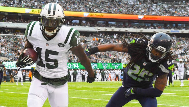 New York Jets wide receiver Brandon Marshall (15) scores a second quarter touchdown ahead of Seattle Seahawks cornerback Richard Sherman (25) during Sunday's game at MetLife Stadium.