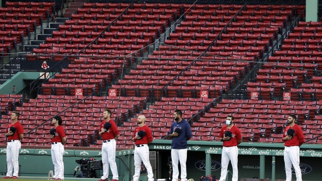Boston Red Sox players stand for the national anthem in front of empty stands prior to an exhibition baseball game against the Toronto Blue Jays, Tuesday, July 21, 2020, at Fenway Park in Boston. (AP Photo/Charles Krupa) ORG XMIT: MACK105