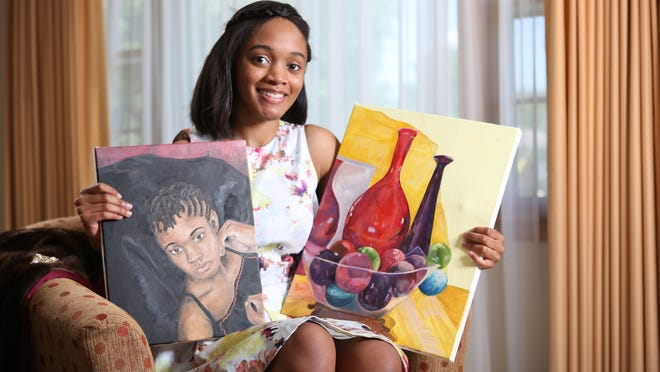 """Artist and fashionista Kellen Jay holds two of her paintings in her parent's Louisville home. Jay describes her own style as """"classic with a twist."""" July 17, 2014"""