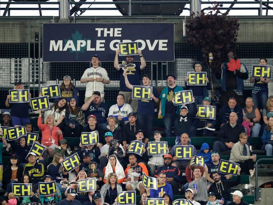 "Fans in the ""Maple Grove,"" the special cheering section for Seattle Mariners starting pitcher James Paxton, hold up ""EH"" signs during the fourth inning of Paxton's Saturday start  against the Detroit Tigers."
