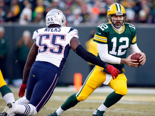 Packers quarterback Aaron Rodgers (12) scrambles under pressure from Patriots outside linebacker Akeem Ayers.