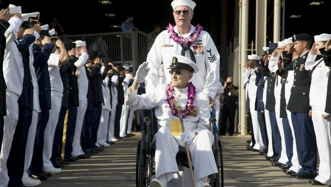 A Navy veteran salutes U.S. service members while leaving the 75th annual remembrance of the attack on Pearl Harbor in Hawaii on Dec. 7, 2016.